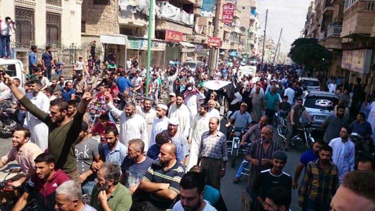Protesters holding Syrian revolution flags and chanting, in Maaret al-Numan, a town in Idlib province, Syria, on Friday.