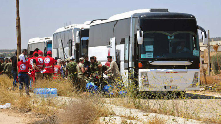 Syrian government forces and Syrian Arab Red Crescent oversee the evacuation by buses of opposition fighters and their families from the southern province of Daraa, Syria, to Idlib in July.