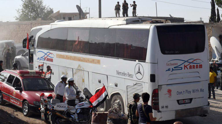 Syrians being evacuated in buses from the two pro-government villages to the crossing between Aleppo and Idlib in July.