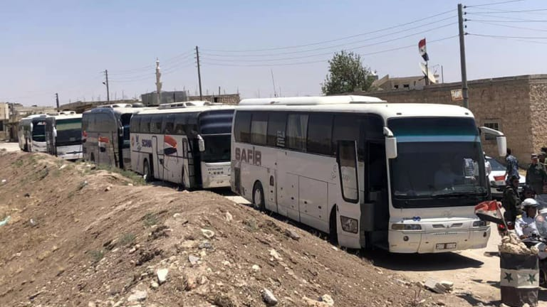 Buses arrive in Tel el-Eis, the crossing between Aleppo and Idlib provinces, as some 7000 people were evacuated from villages run by rebels in July.