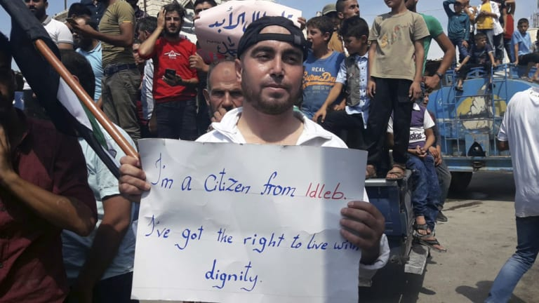 A man holds a placard in Harim, in Idlib province, on Friday as part of a day of protests against Syrian President Bashar al-Assad and his troops' imminent offensive against Idlib.