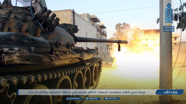 This photo provided  by the al-Qaida-affiliated Ibaa News Network, shows a tank of the al-Qaida-linked coalition known as Hay'at Tahrir al-Sham, Hay'at Tahrir al-Sham, Arabic for Levant Liberation Committee, firing at Syrian troops and pro-government gunmen in rural Aleppo, Syria.