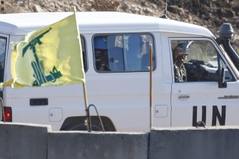 United Nations personnel drive past a Hezbollah flag on a concrete barrier in southern Lebanon on the border with Israel on Wednesday. The US wants a reduction of UN peacekeeping forces in Lebanon.