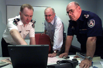 Then prime minister John Howard is briefed by Shane Fitzsimmons (left) and Phil Koperberg (right) of the RFS in 2001 about a fire that devastated Warragamba in the Blue Mountains.