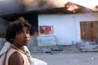 September 1999: A girl walks by a burning house in Dili, East Timor, two days before the arrival of Australian peacekeeping troops.