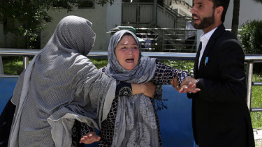 A woman shouts and cries at a hospital after she lost her son in the suicide attack on a voter registration centre.