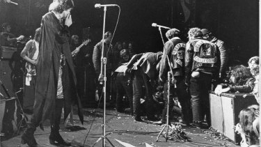 Mick Jagger looks on as the Hells Angels drag an unidentified person onstage at the Altamont  rock festival, California, Dec 6, 1969.