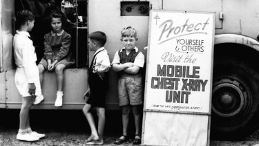 Children wait outside a mobile unit while their parents are being X-rayed inside.