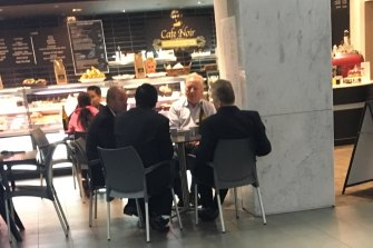 Daryl Maguire (left of image facing), unknown male 1 referred to as Ron (white shirt), Michael Hawatt (right, back to camera), Charbel Demian (left, back to camera). All males seated at the Cafe Noir 233 Castlereagh Street, Sydney.