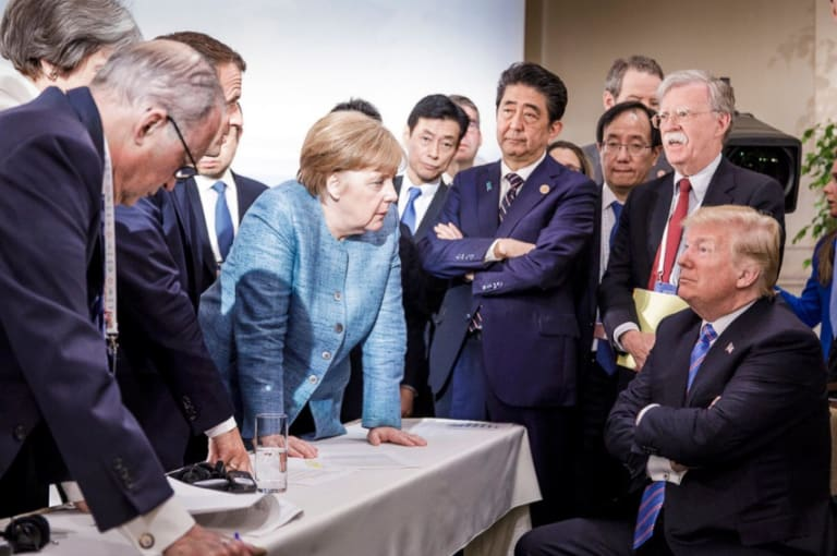 German Chancellor Angela Merkel, centre, speaks with U.S. President Donald Trump, seated at right, during the G7 Leaders Summit in La Malbaie, Quebec, Canada.