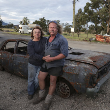 Gail and Brad Rayer with their burnt out 1971 Ford Falcon XY GTHO after bushfires destroyed large parts of their property and auto mechanic business near Cobargo, NSW.