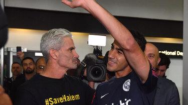 A jubilant Hakeem al-Araibi walks out of Melbourne Airport alongside former Socceroos captain Craig Foster.