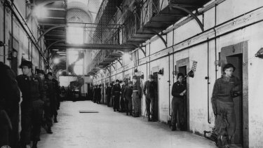 An individual guard stands before each cell in the main section of the Nuremberg jail where Nazi war criminals are lodged. The cells of Hermann Goering and Rudolf Hess are at the far right.