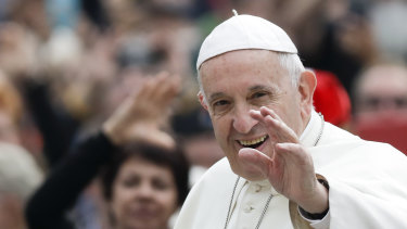 Pope Francis waves to faithful as he arrives for his weekly general audience.
