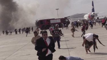 People run after an explosion at the airport in Aden, Yemen, shortly after a plane carrying the newly formed cabinet landed.