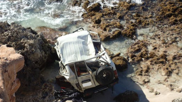 The roof of the white Toyota LandCruiser caved in on impact after it plunged 20 metres off the cliff.