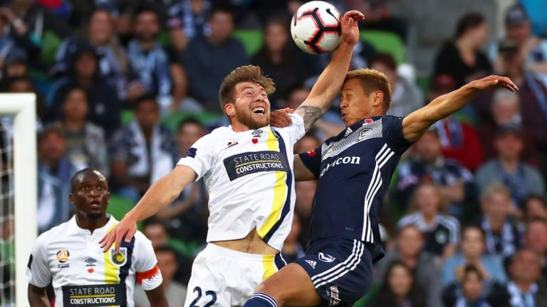 All in: Jacob Melling of the Mariners clashes with Keisuke Honda.