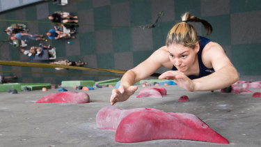 Oceana Mackenzie jumps and grasps for a hold in sport climbing practice for the Tokyo Olympics.