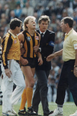 Dermott Brereton receives attention from medical staff after being flattened by Geelong's Mark Yeates in the opening moments of the 1989 Grand Final.