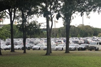 Cars parked on fields near Kippax Lake at Moore Park during an event.