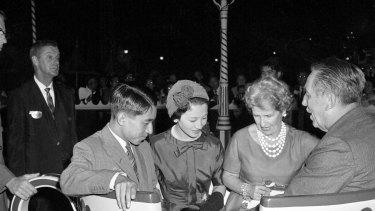 Le prince héritier Akihito et la princesse Michiko du Japon partent prendre la tasse de thé du Chapelier avec Walt Disney et sa femme Lillian Disney à Disneyland à Los Angeles.