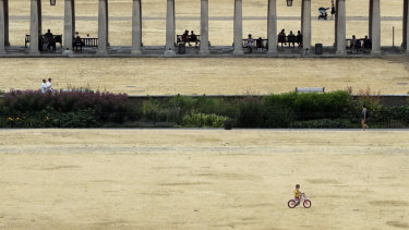 A child cycles on parched grass from the lack of rain in Greenwich Park in Britain.