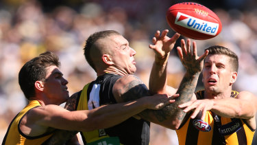 Up for grabs: Richmond's Dustin Martin attempts to mark despite the attentions of Hawthorn's Jaeger O'Meara and Luke Breust.