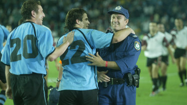 Joaquin Pastore, now Uruguay's attack coach, celebrates with a NSW Police officer after beating Georgia at the 2003 World Cup.