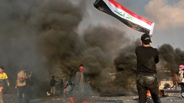 A protester waves the national flag during clashes with security forces in central Baghdad.