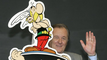 French author and illustrator Albert Uderzo waves from behind a cardboard cutout showing his comic heroes Asterix and Obelix at the 57th Frankfurt Book Fair, 2005.