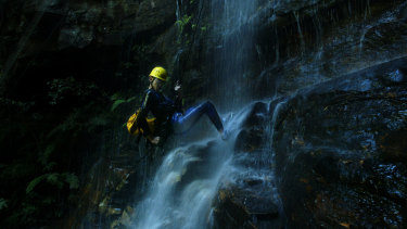 A tourist abseils down a waterfall in the Empress Falls Canyon in the Blue Mountains.