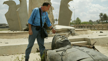 Paul McGeough looks down at one of the many felled Saddam Hussein statues in Baghdad during the 2003 invasion.