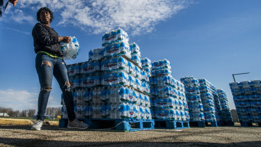 Volunteers load cases of water into vehicles in Flint, Michigan, in April.