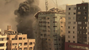 A building housing various international media, including The Associated Press, collapses after an Israeli airstrike on Saturday.