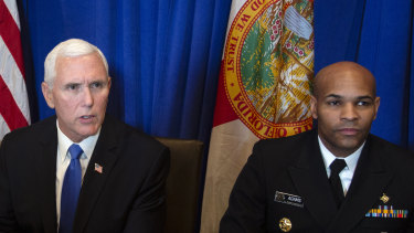 US Vice President Mike Pence, left, speaks while Vice Admiral Jerome Adams, US Surgeon General, looks on.