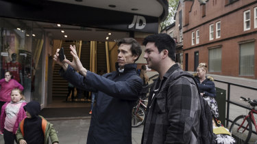 Rory Stewart, center, a candidate for prime minister, takes a selfie with a supporter as he campaigns in Wigan, England.