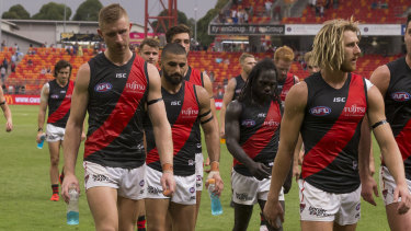 Dyson Heppell (right) leads the defeated Bombers from the field.