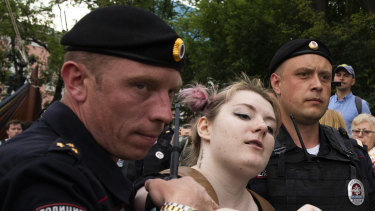 Police officers detain a woman during a march in Moscow, Russia.