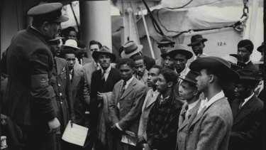 A Royal Air Force recruiting officer speaks to Jamaicans as they arrive in the UK aboard Empire Windrush in June, 1948.