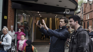 Rory Stewart, centre, a candidate for prime minister, takes a selfie with a supporter as he campaigns in Wigan, England.