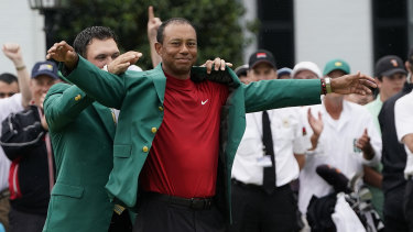 Glory days: Last year's Masters winner Patrick Reed helps Tiger Woods put on the famous green jacket.