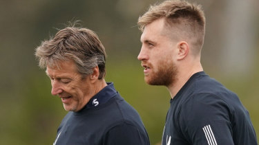 Storm coach Craig Bellamy (left) talks to Cameron Munster (right) during Tuesday training at Gosch's Paddock.