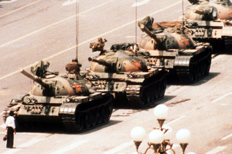 A lone protester clutching a shopping bag prevents a line of tanks from reaching Tiananmen Square, Beijing on June 4, 1989.