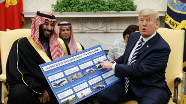 US President Donald Trump shows a chart highlighting arms sales to Saudi Arabia during a meeting with Saudi Crown Prince Mohammed bin Salman in the Oval Office of the White House in Washington in March, 2018.