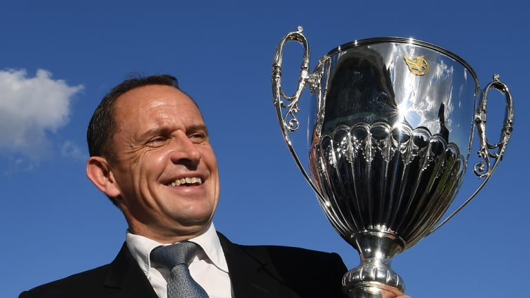 Trainer Chris Waller holds the trophy after jockey James McDonald rode The Autumn Sun to victory.
