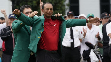 Last year's Masters winner Patrick Reed helps Tiger Woods put on the famous green jacket.
