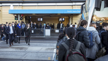 Commuters leaving South Yarra train station, heading for a tram, where a fence blocks part of the footpath.