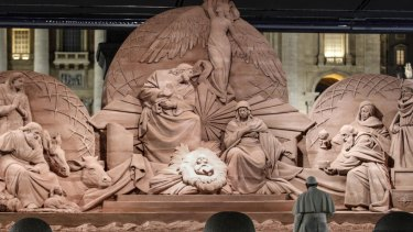 Pope Francis prays in front of a nativity scene.