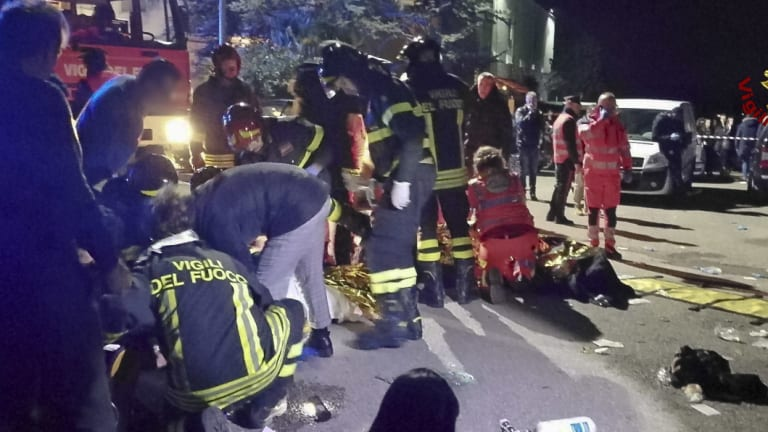 Rescuers assist injured people after the nightclub stampede.