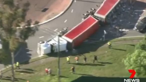 B-Double rolls on Brisbane roundabout, spilling rubbish everywhere